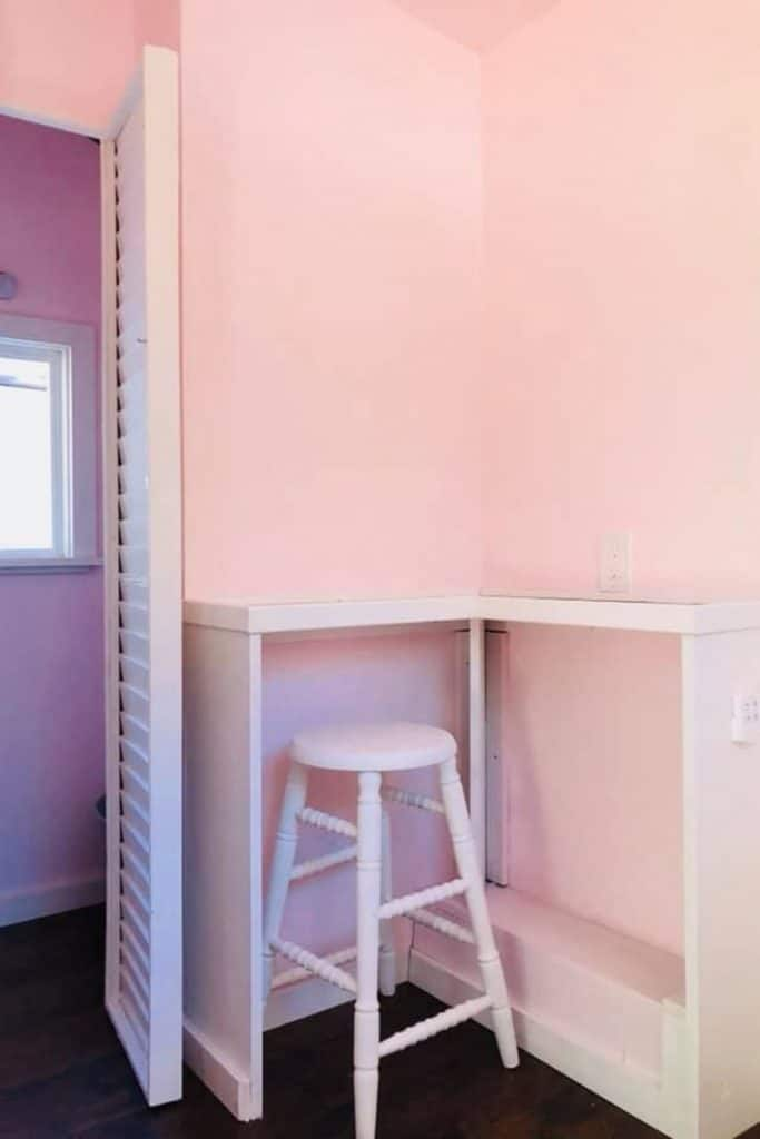 White shelf with white stool against pink wall