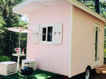 Light pink camper with small umbrella and hibatchi on green table