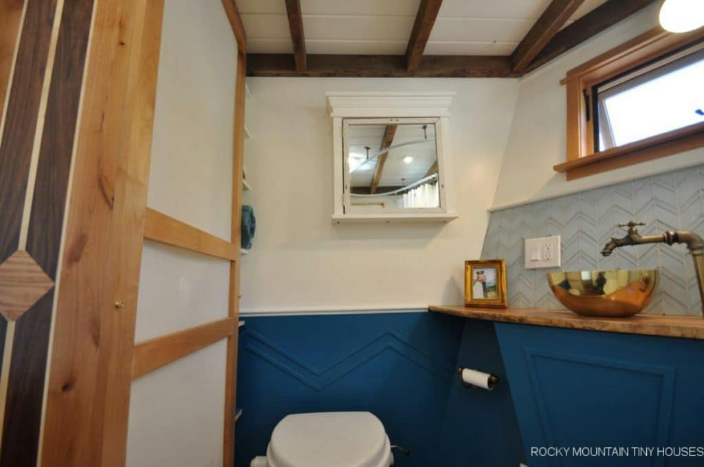 Bathroom mirror above toilet with white and blue walls
