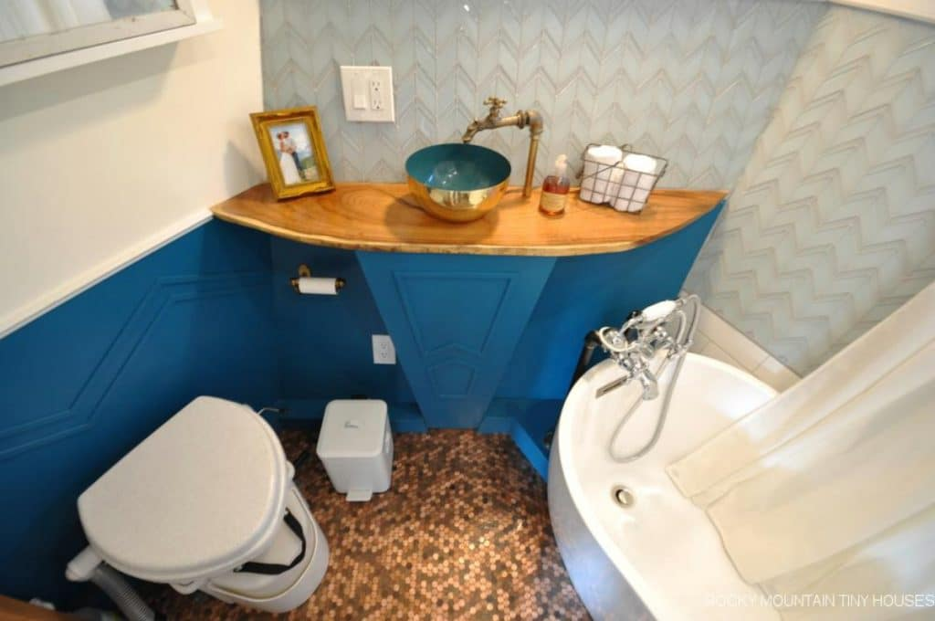 Bathroom with large white soaking tub composting toilet and blue wainscotting