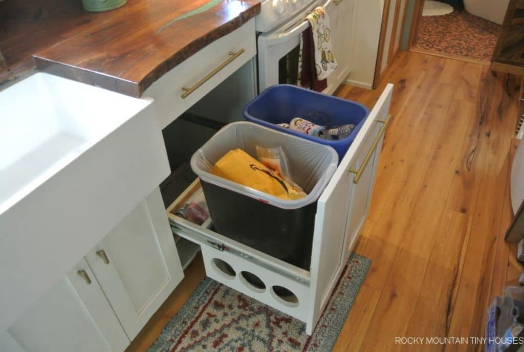 Garbage cans inside drawer under white cabinet with butcherblock counters