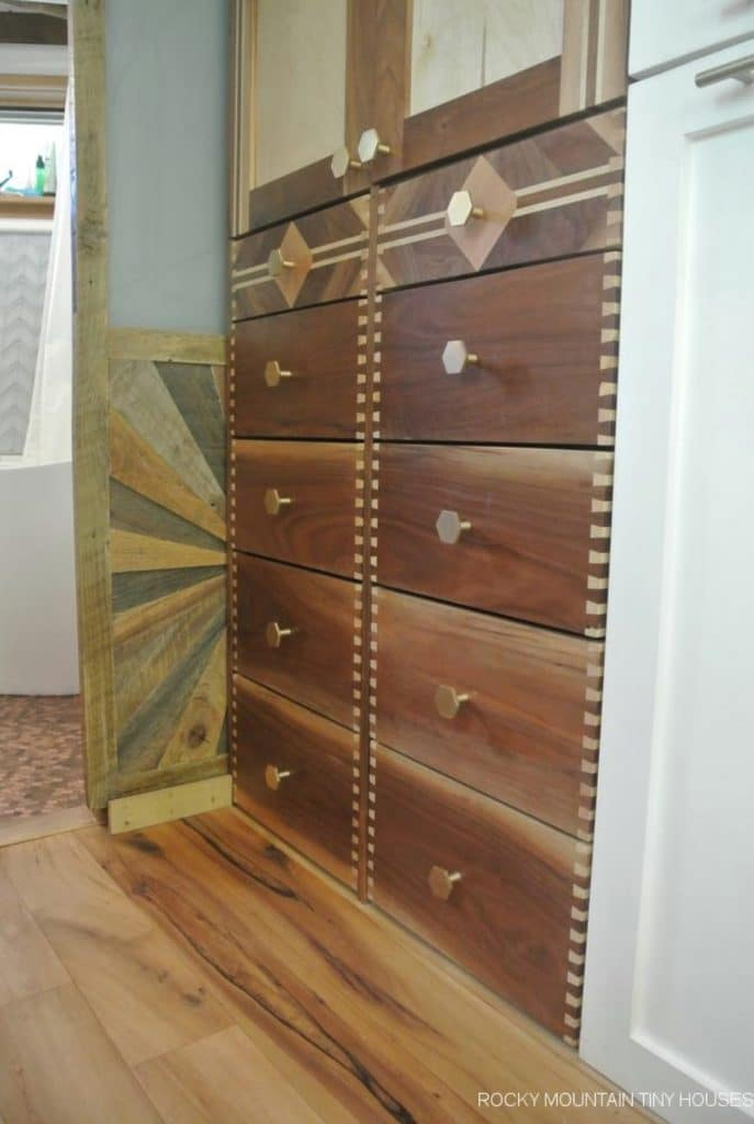 Built in chest of drawers in tiny home with mural behind