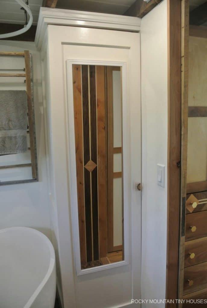 Door in bathroom with full sized mirror