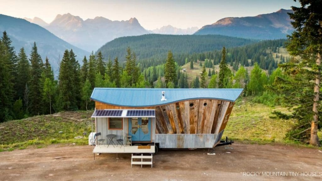 Tiny house with sloped roof on lot by mountains
