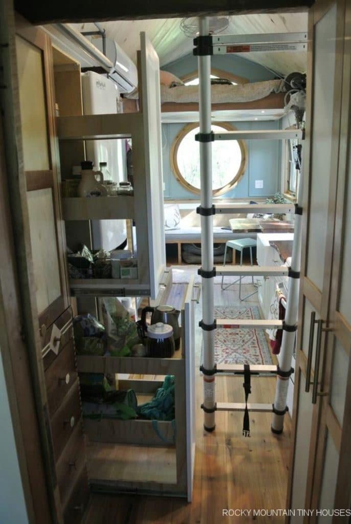 Ladder to loft next to open kitchen cabinets