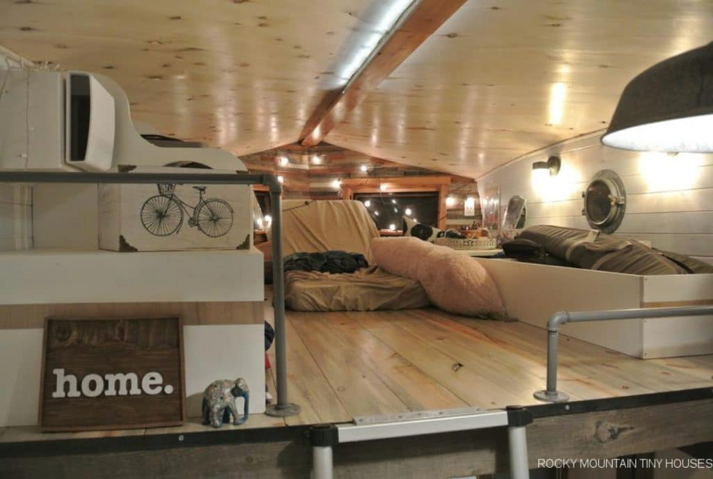 View into tiny home loft with light wood ceiling and floor