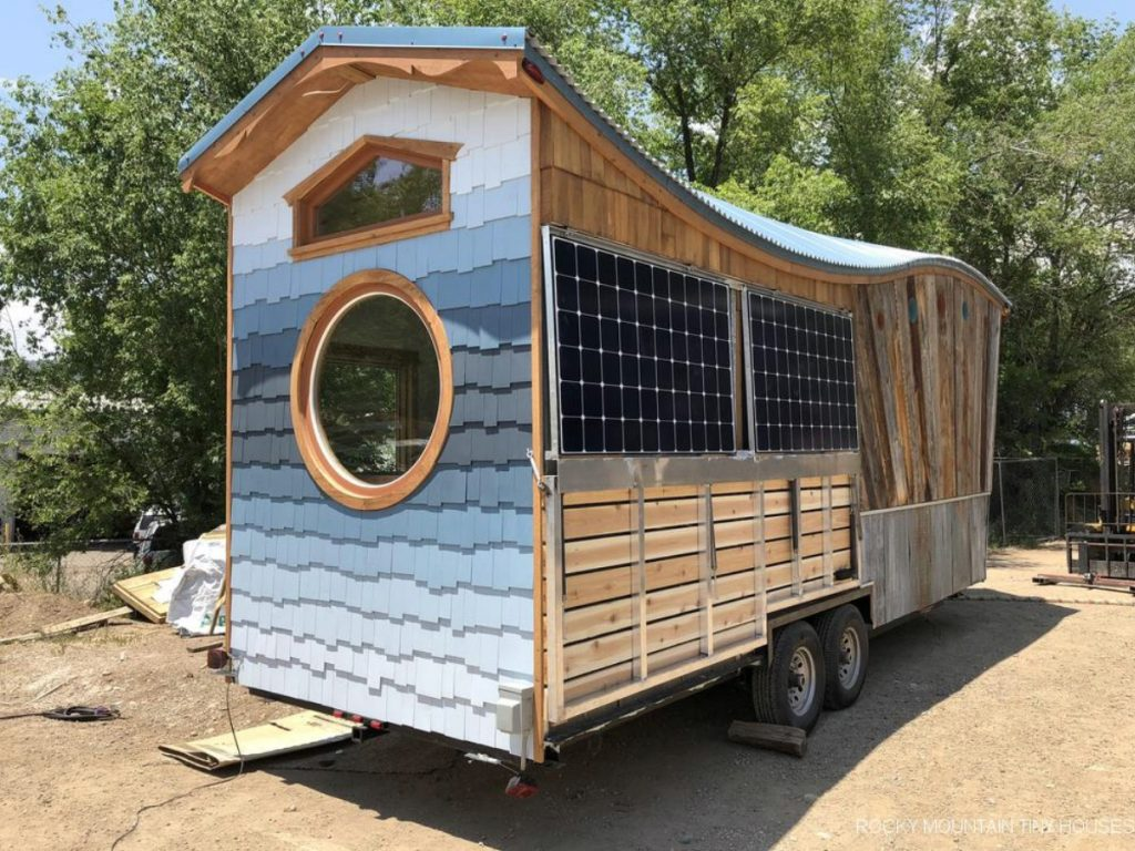 Side of tiny home with solar panels and round windo at end
