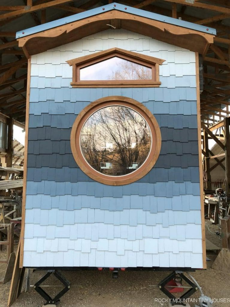 Blue ombre siding on end of tiny home with round window