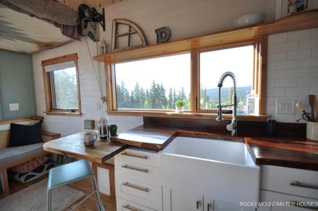 White farmhouse sink in butcher block counter in kitchen