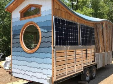 Side and end of tiny home with round window and blue ombre siding
