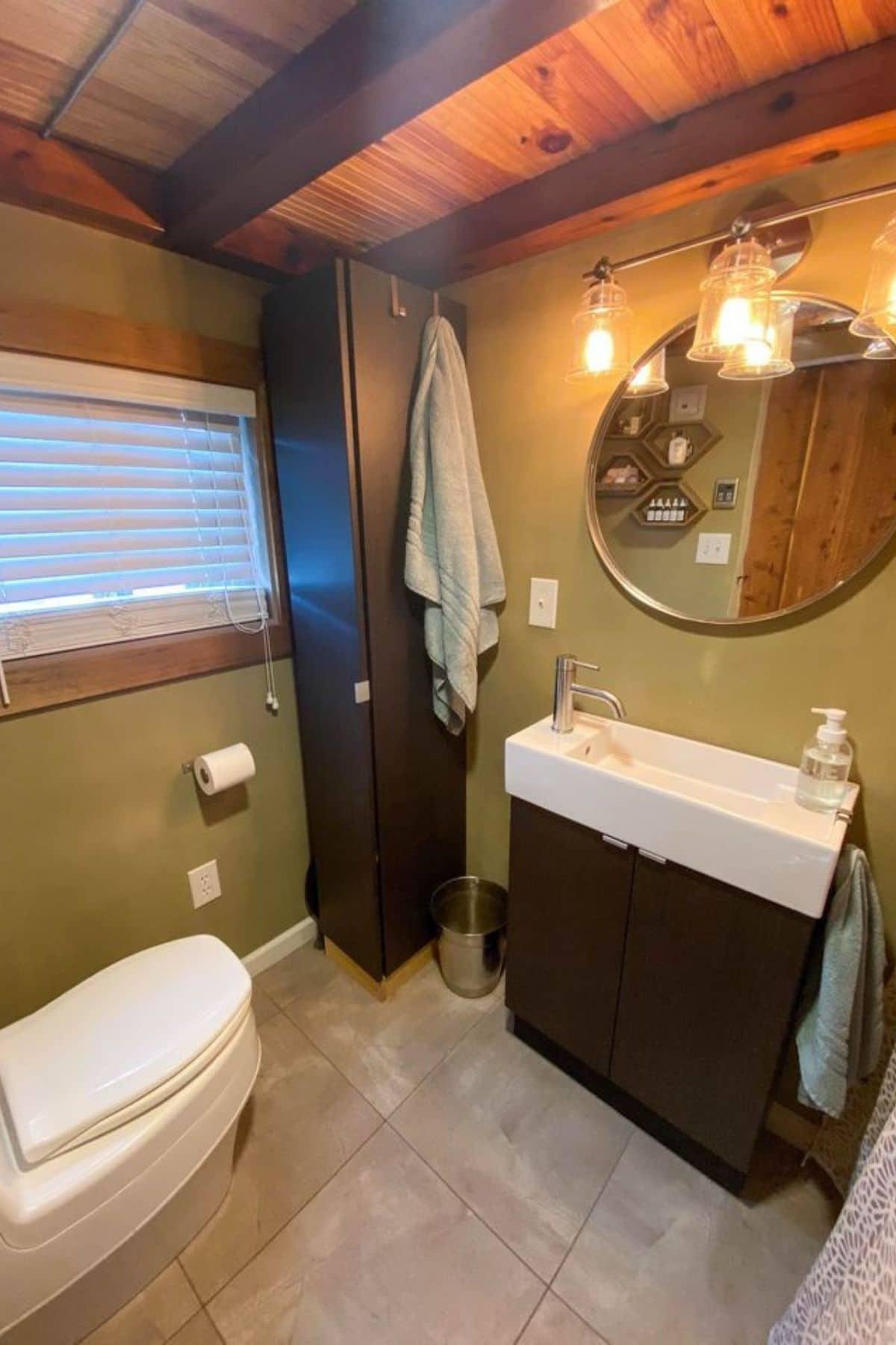 Green walls of bathroom with dark wood vanity and white sink