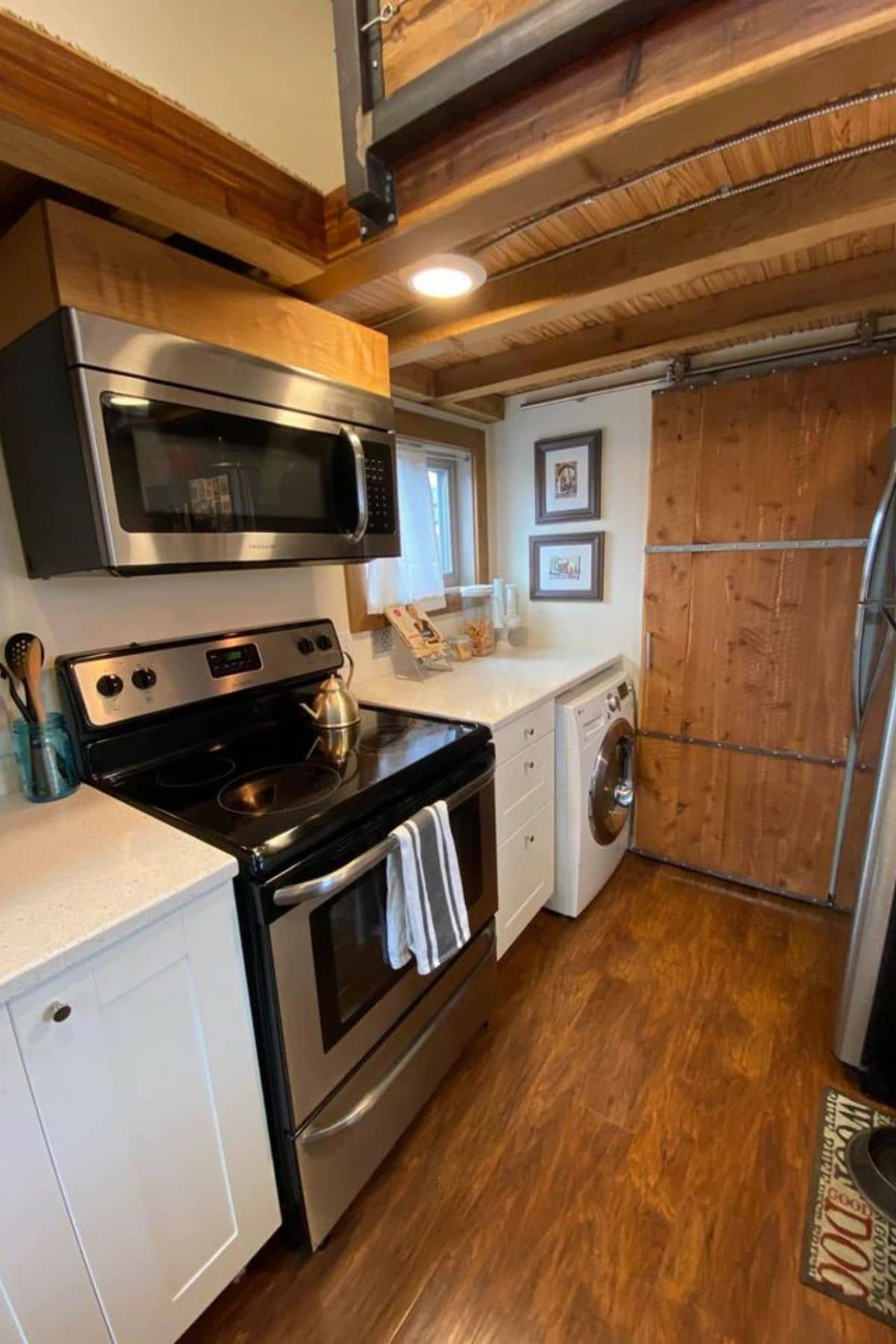 Stainless steel stove in white cabinets of tiny house kitchen