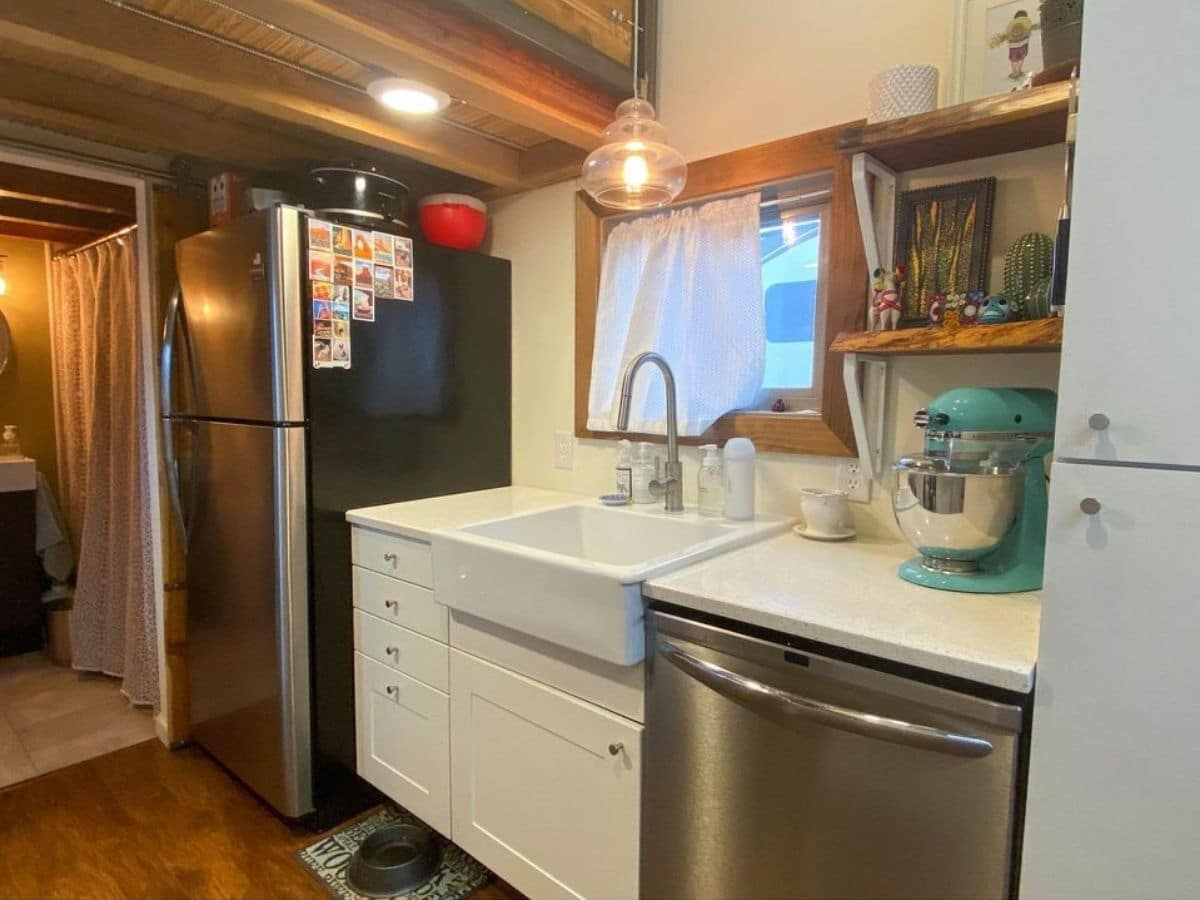 Refrigerator in background with dishwasher in foreground of white cabinets