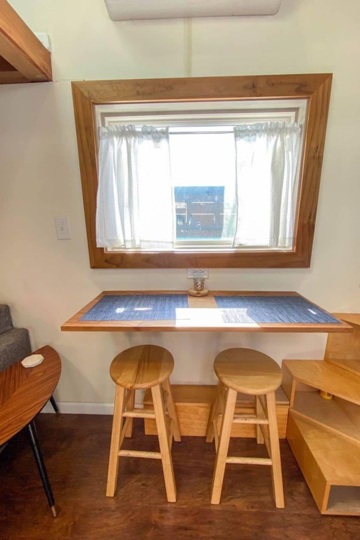 Blue and wood shelf under large window with light wood stools