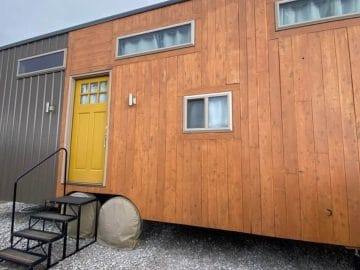 Wood siding on tinyhouse with yellow door