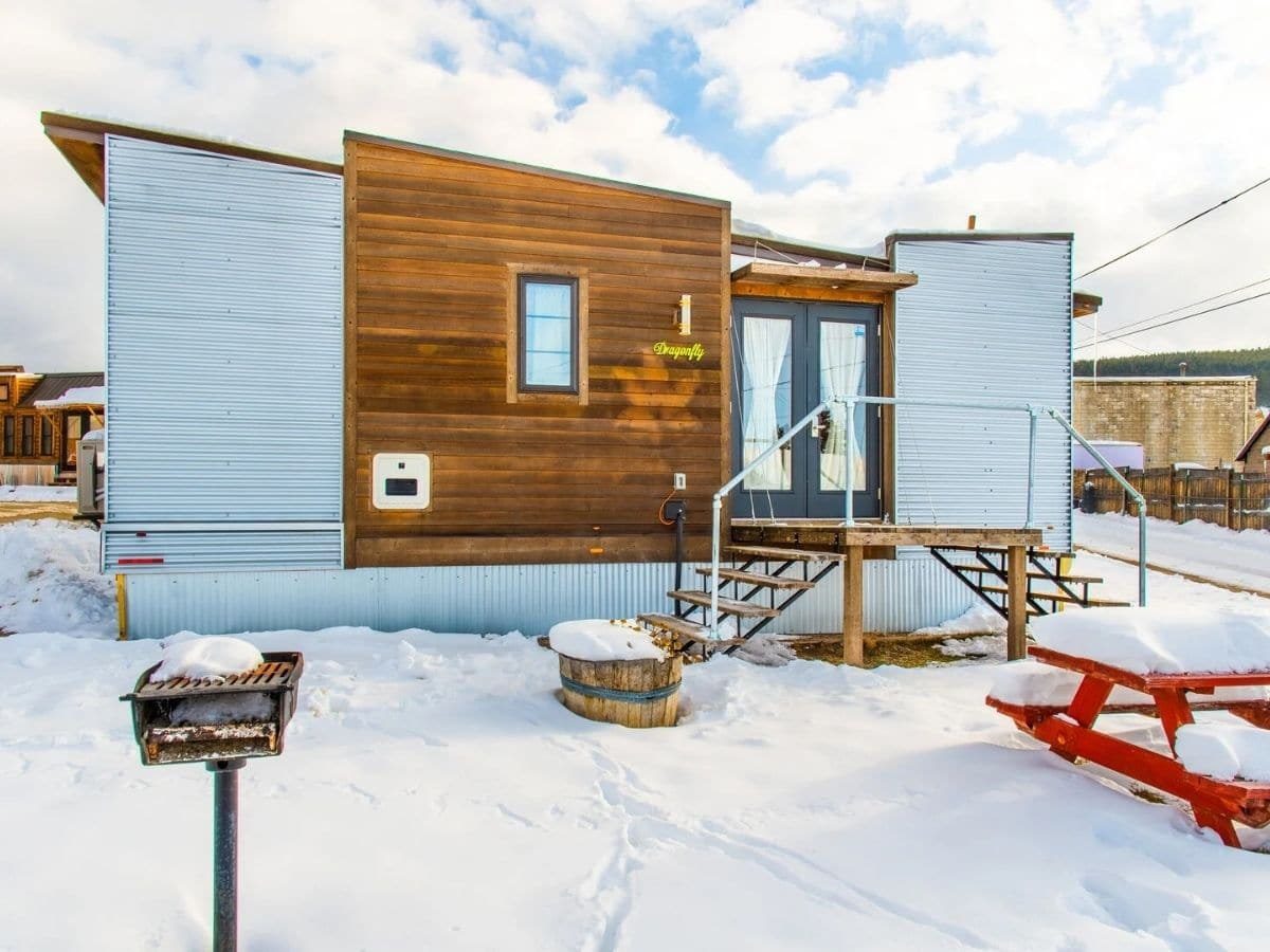 Light blue and wood siding on tiny home with snow