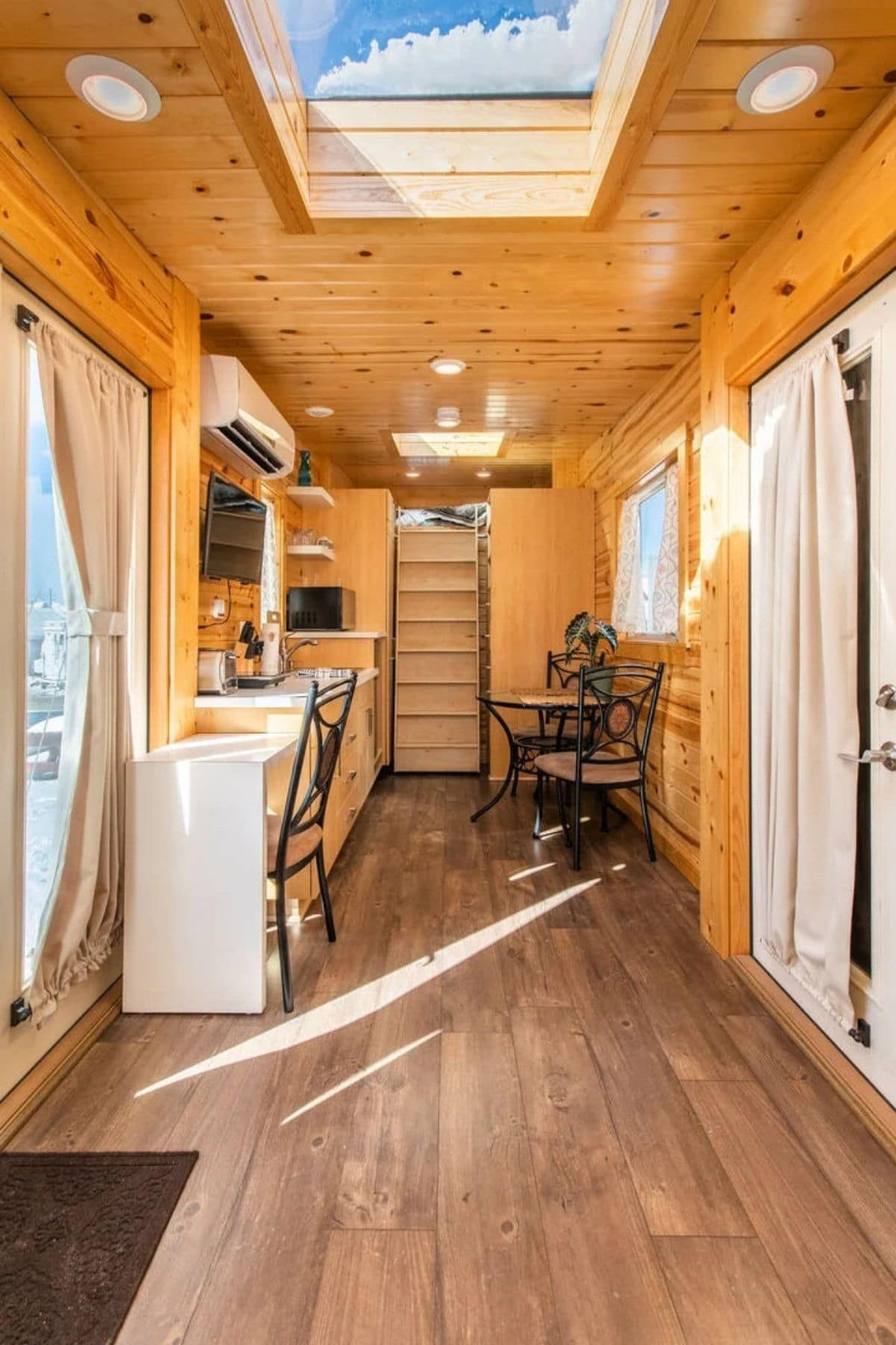 Natural wood walls in tiny home with kitchen on left