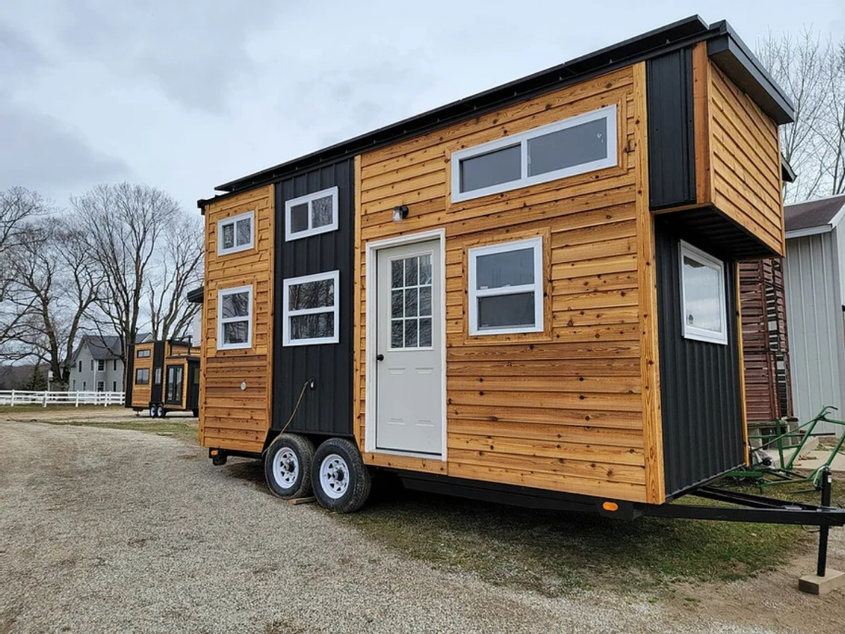 Tiny home on lot with wood and black siding and white door