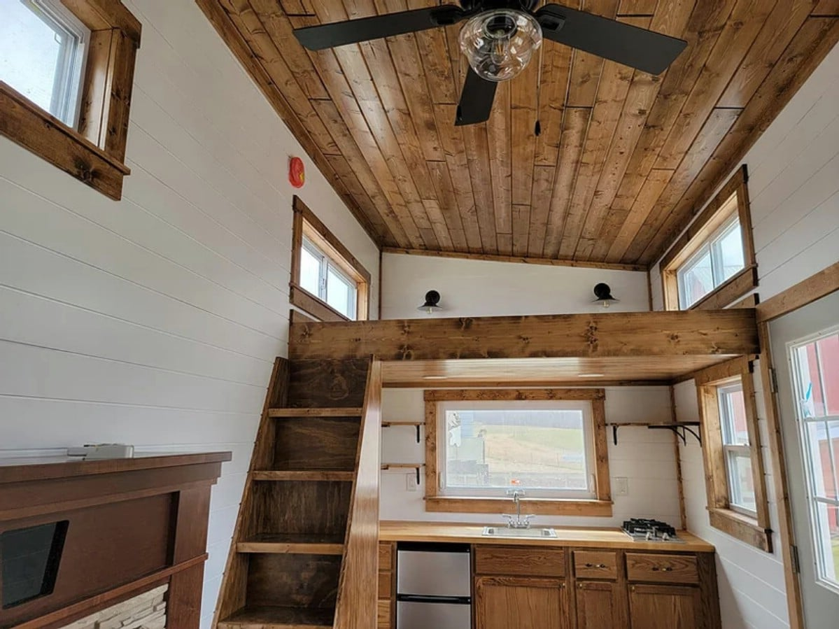 View up to wood ceiling with fan hanging over middle of room