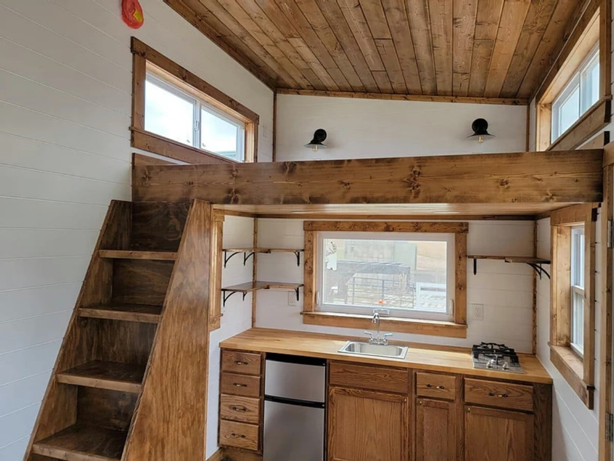 Loft above kitchenette with wooden staircase to left