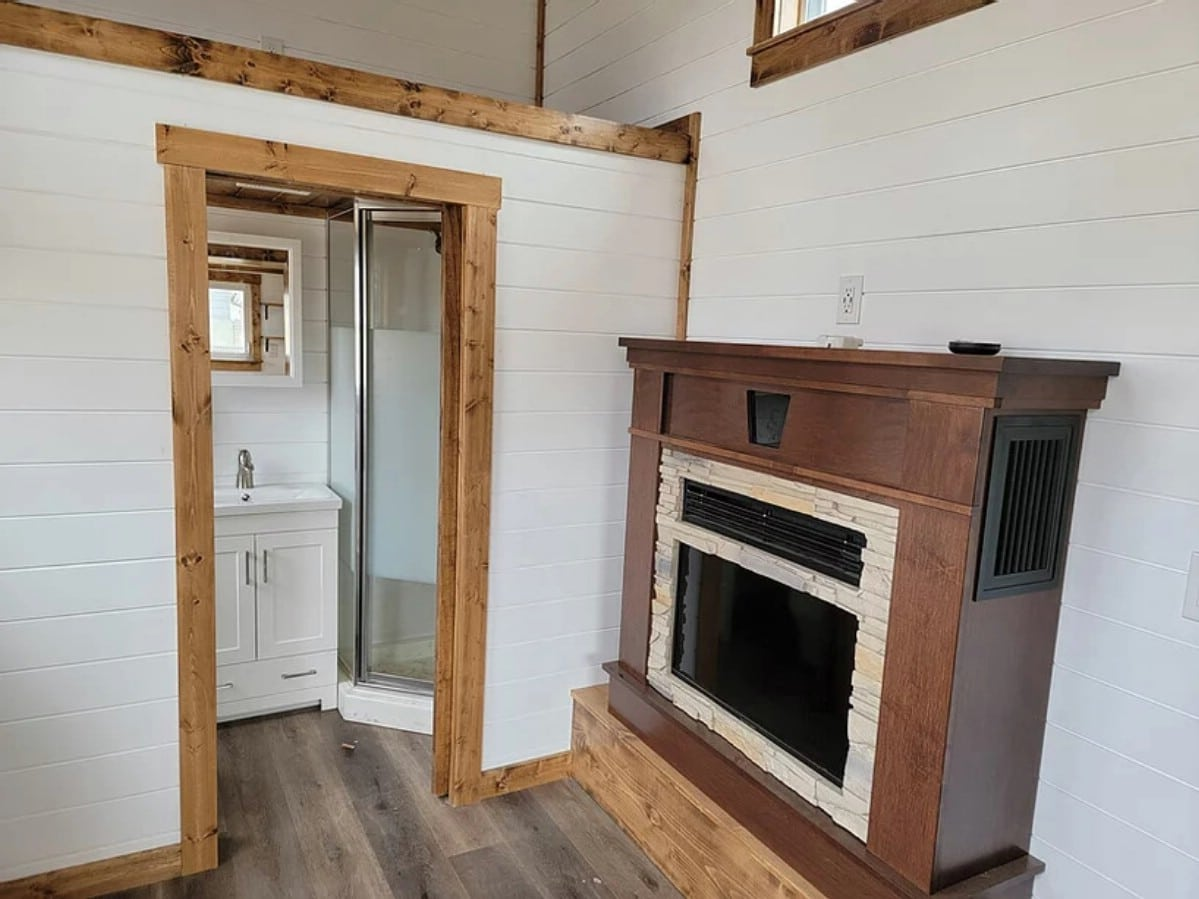 Fireplace in wood inset against white wall next to open bathroom door