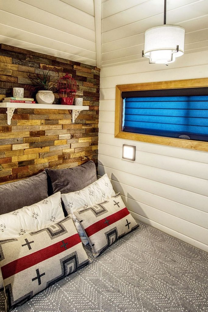 Corner bedroom with shiplap and fake brick wall next to bed with gray bedding