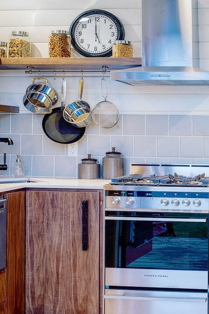 Dark wood kitchen counter by stainless steel gas range with pots hanging from upper cabinets