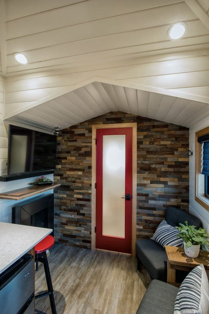 Fake brick wall with red trimmed frosted glass door in center