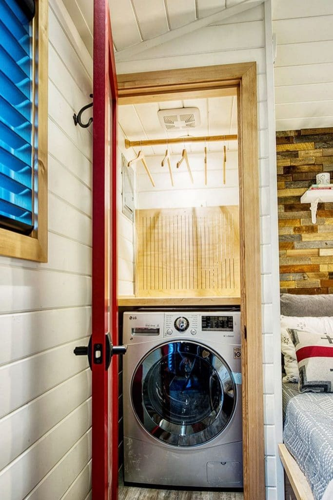 Laundry unit inside closet with red door