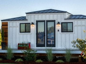 White tiny house with tall roof in center and dark trim
