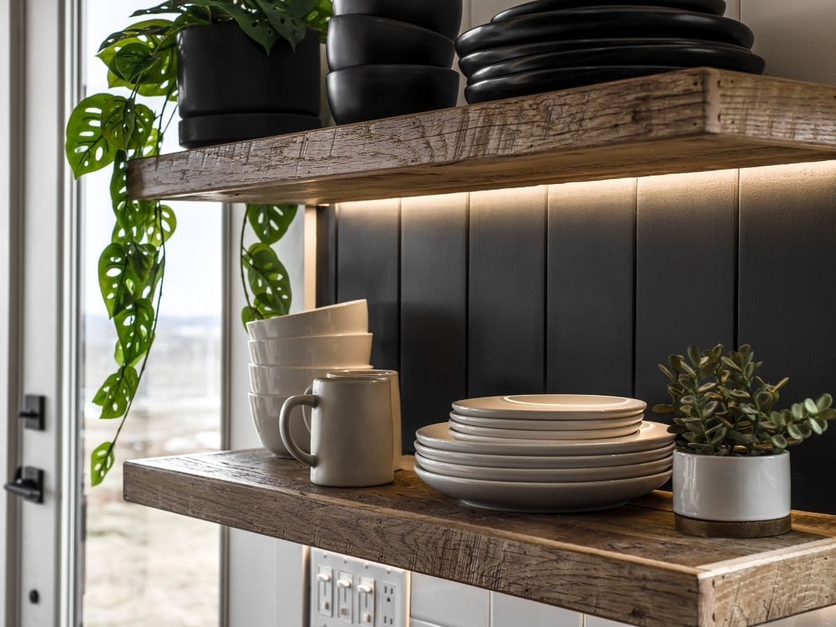 Wooden shelf with stack of plates and cups
