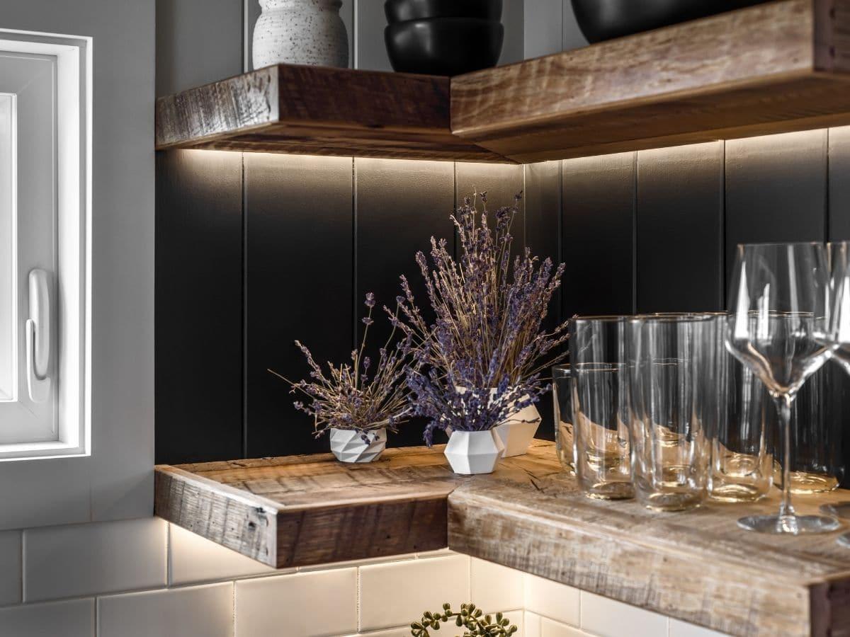 Corner floating shelves against black wall