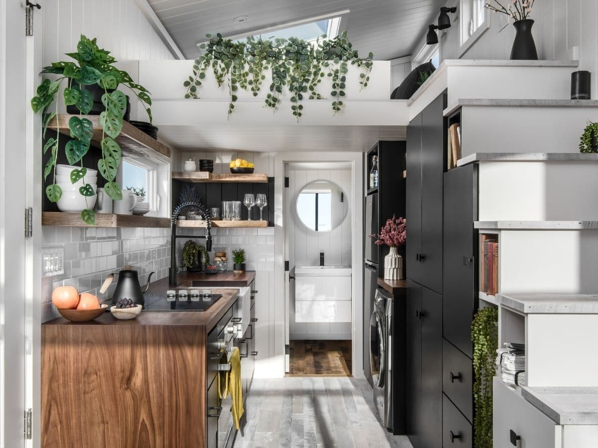 View into tiny house kitchen with black cabinets and dark wood trim