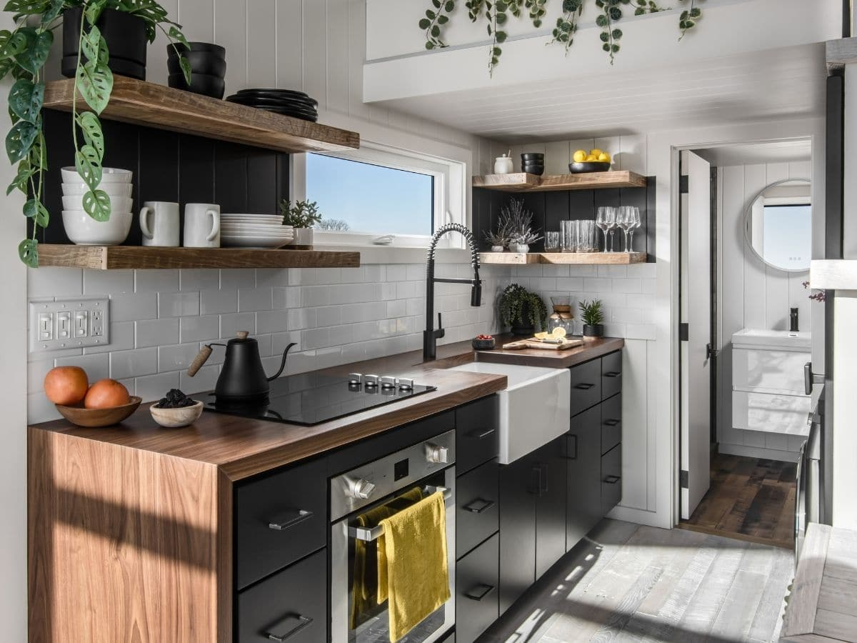 Black cabinets with oven built in next to white sink in kitchen