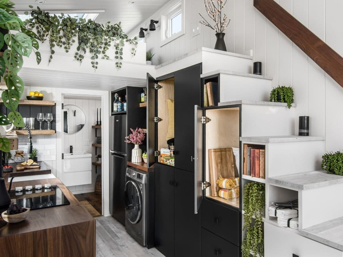 Doors open on black cabinets under white stairs