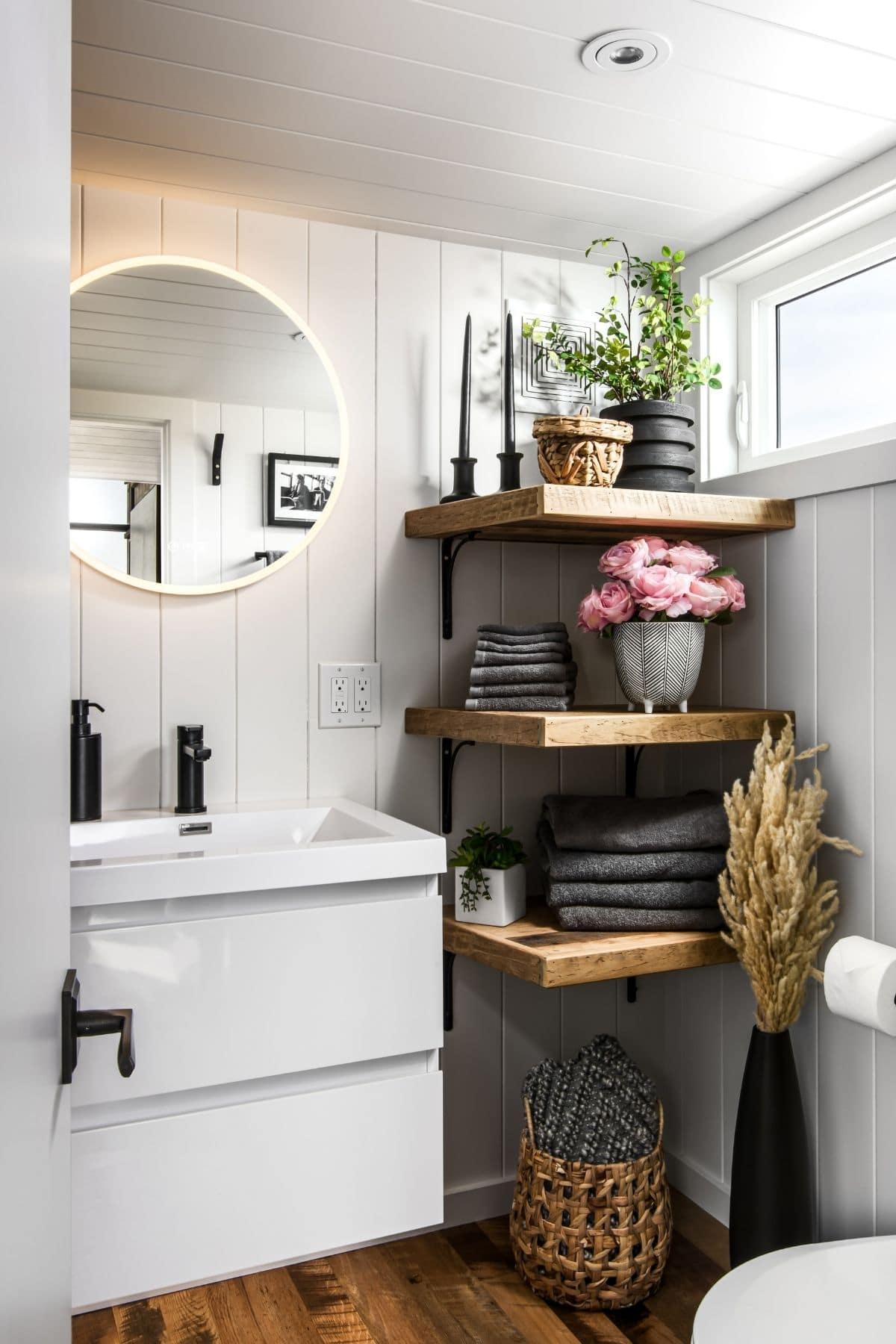 White vanity below round mirror next to open wood shelf in bathroom