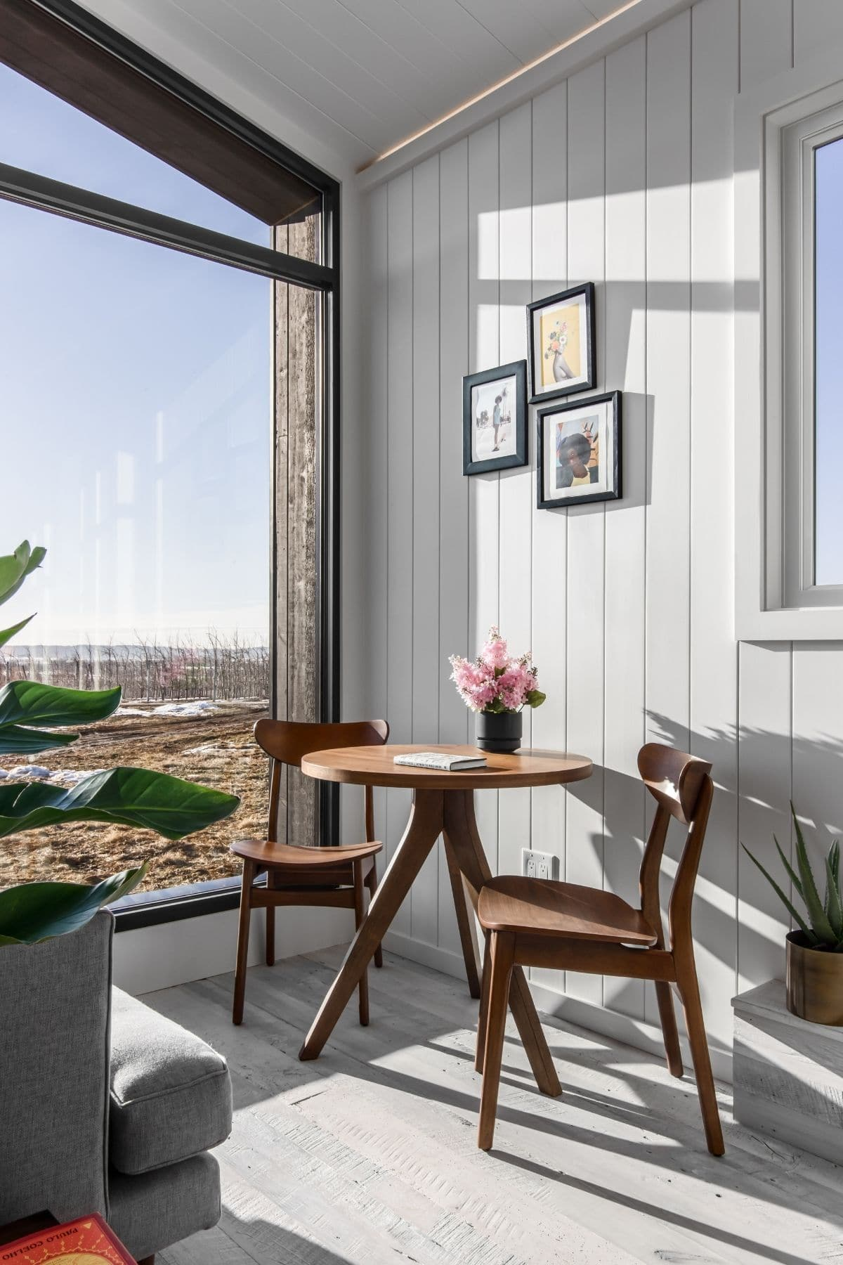 Two wooden chairs next to wood table by open window