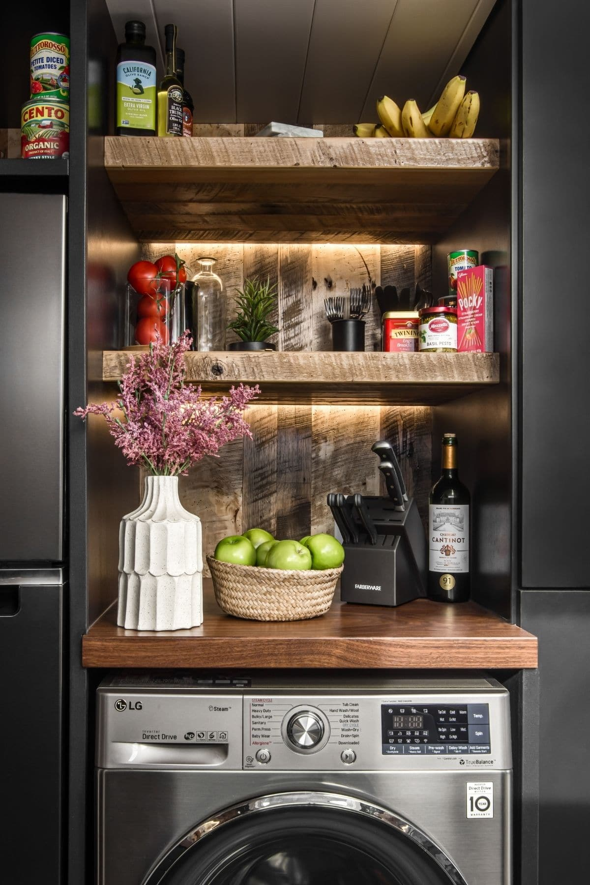 Open wood shelves above washing machine between black cabinets