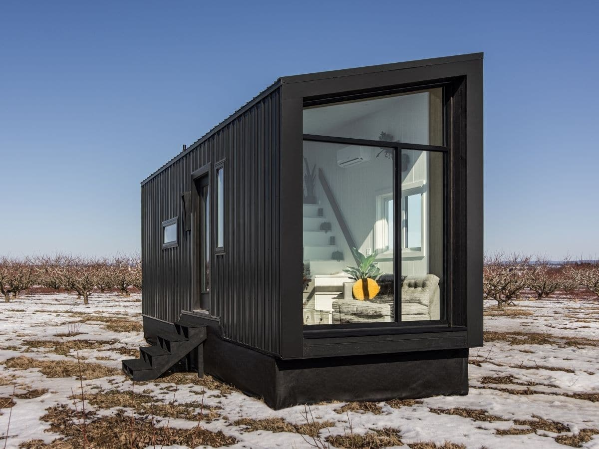 Side of black tiny home with asymmetric roof and glass end