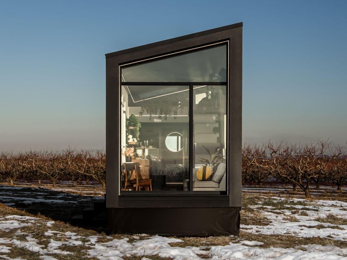 Front of black tiny home with glass end in field