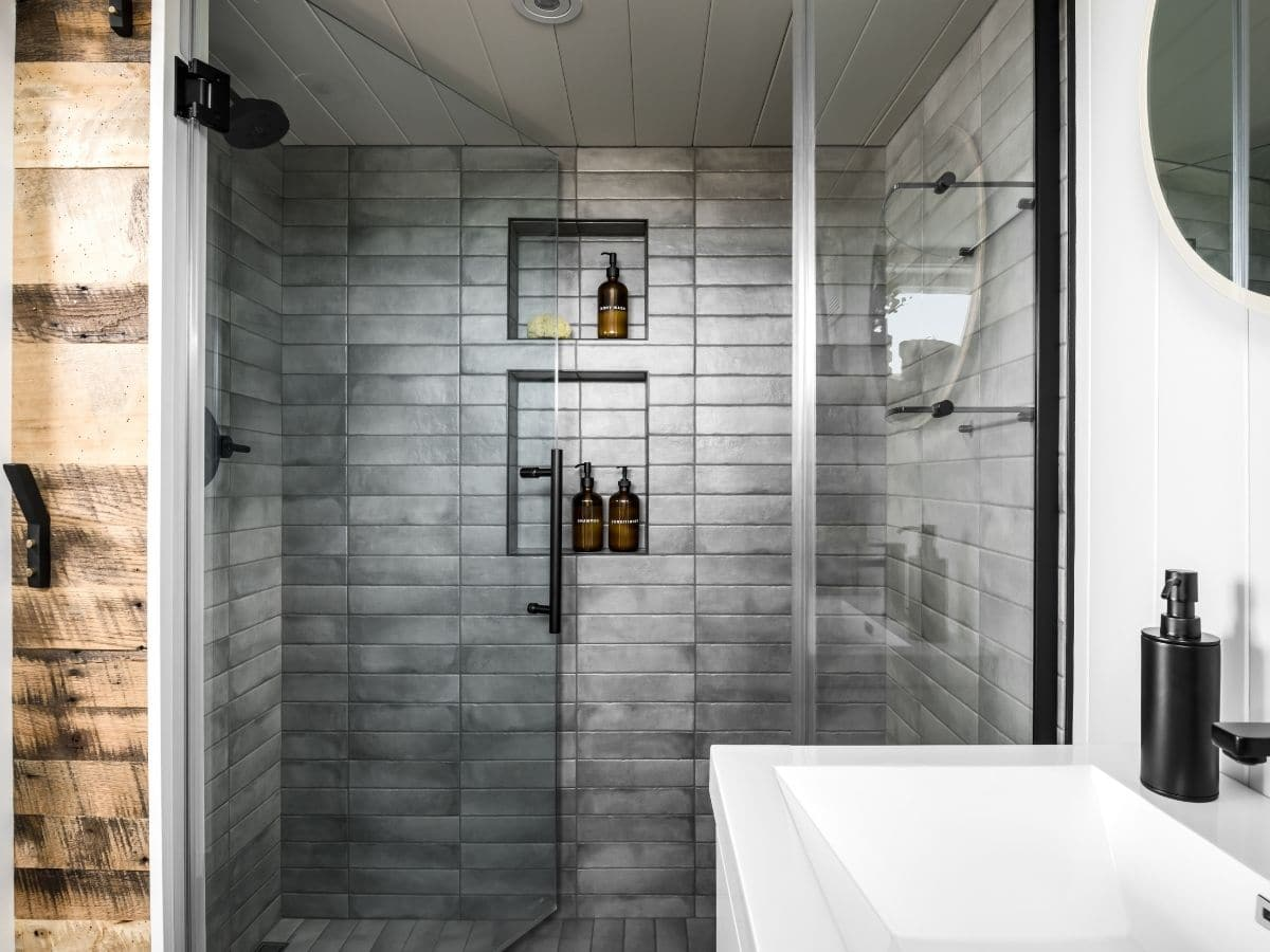 Large shower with gray tile and glass door