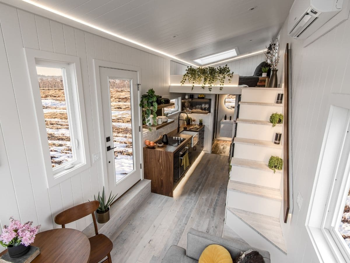 View from front of tiny home in toward white stairs to loft