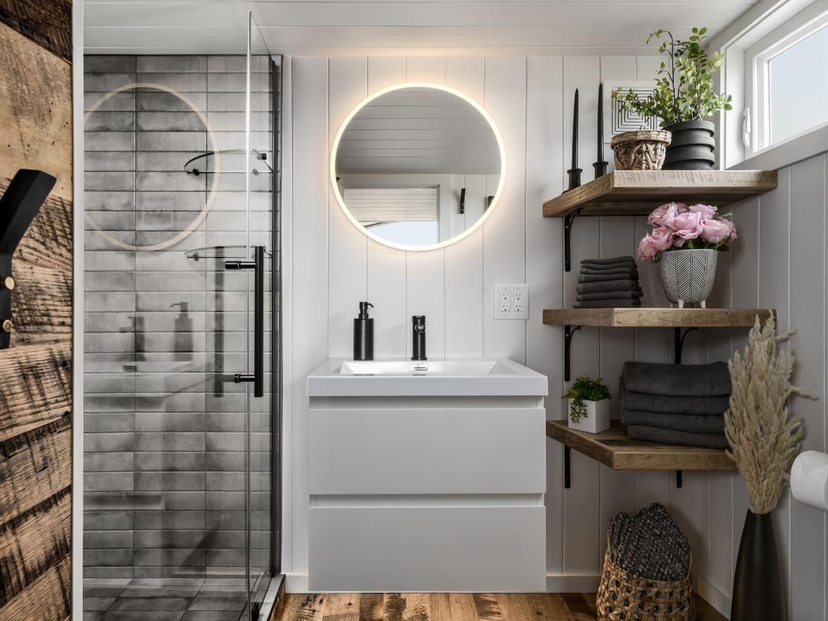 Bathroom with vanity in center and glass door to shower on left