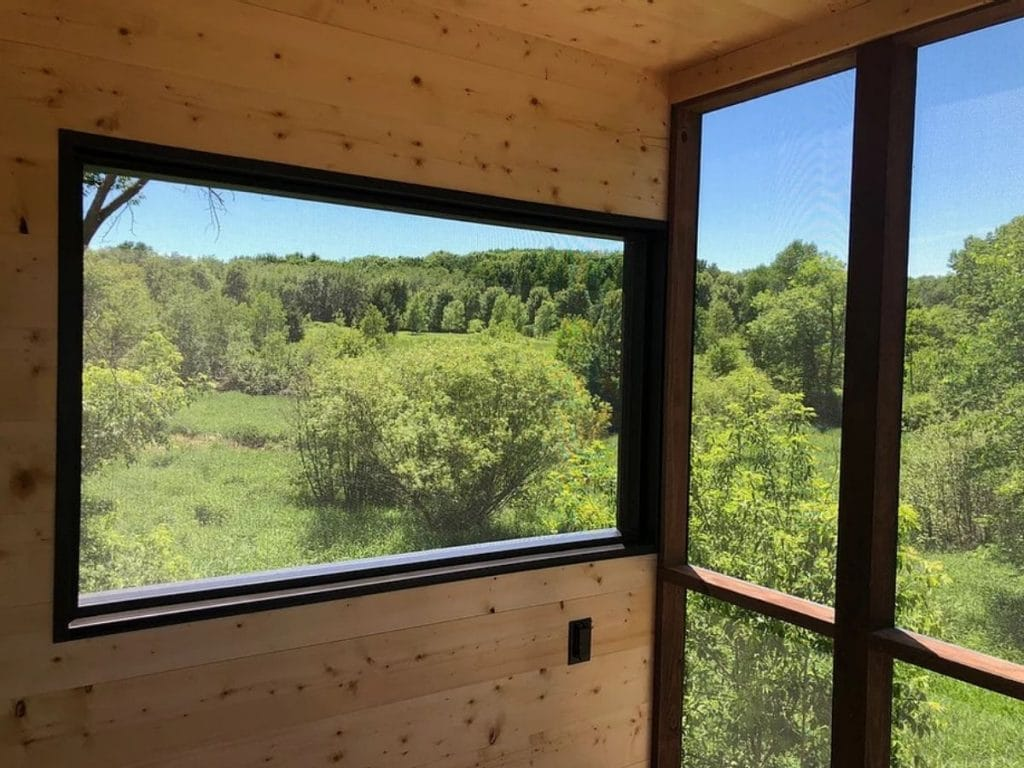 Large window in porch surrounded by black trim looking out at trees