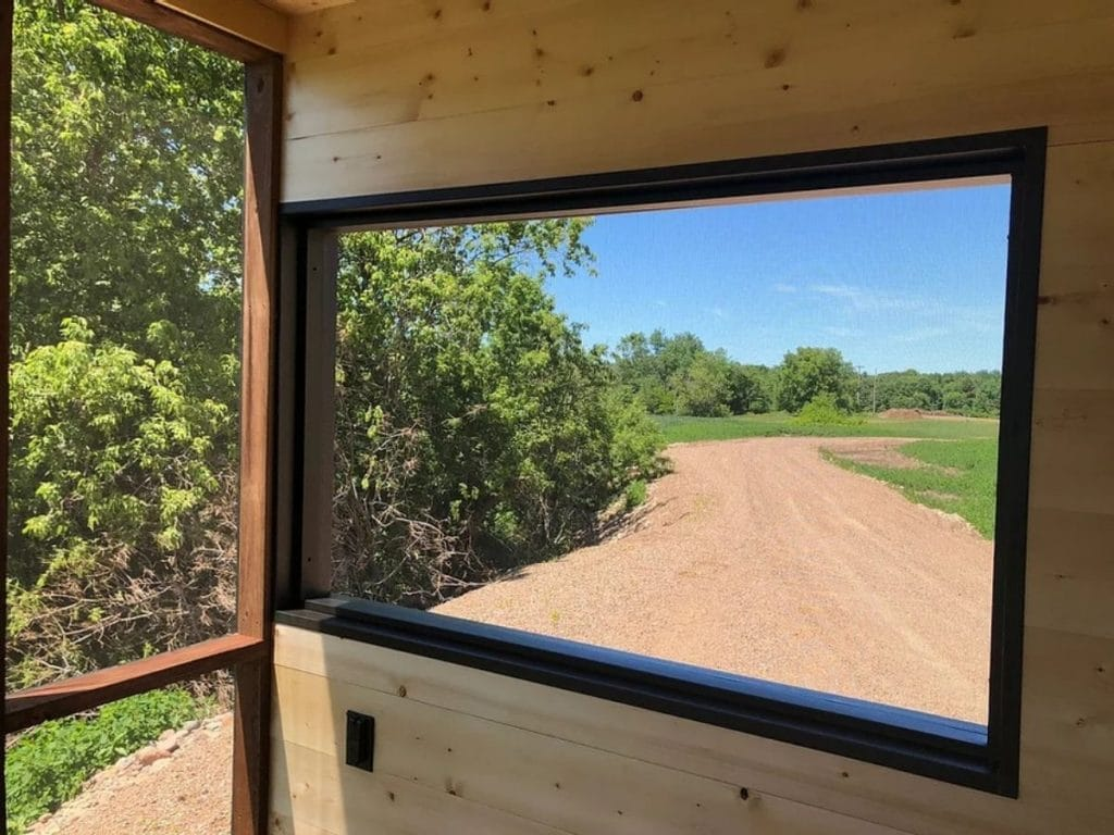 Large window in natural wood wall next to glass panel looking out at road