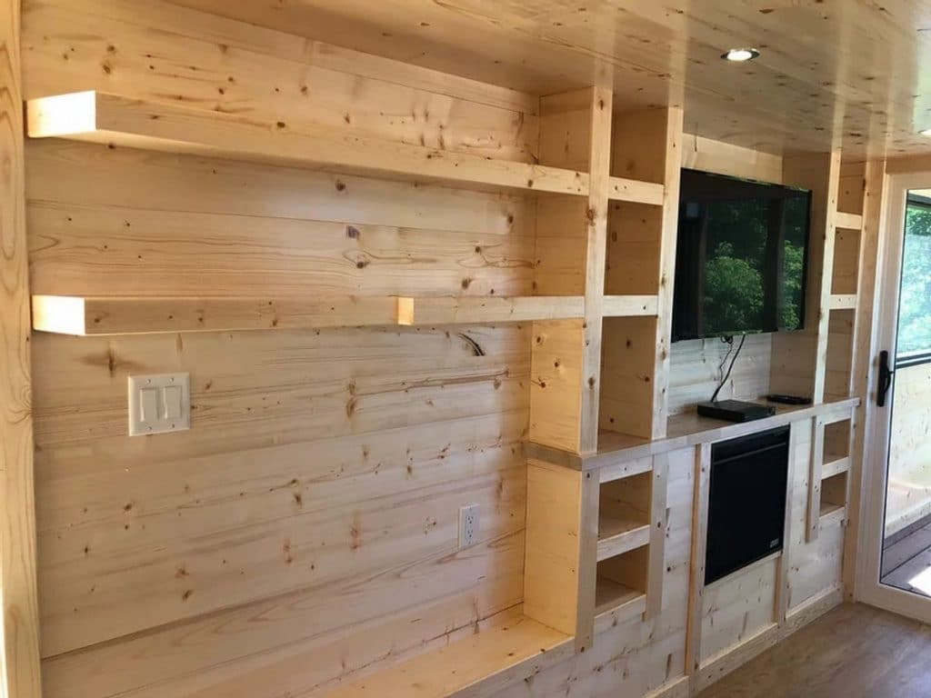 Built in natural wood shelves around fireplace and television against wall