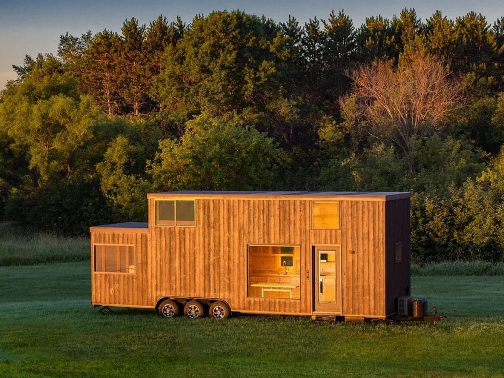 Medium wood stained siding on tiny home sitting in field