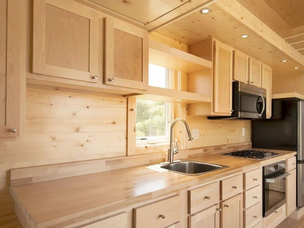 Light wood cabinets and walls in galley kitchen with stainless steel stove