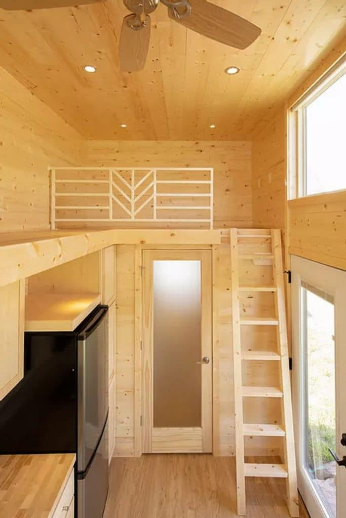 View into small loft space with wood ladder above frosted glass door