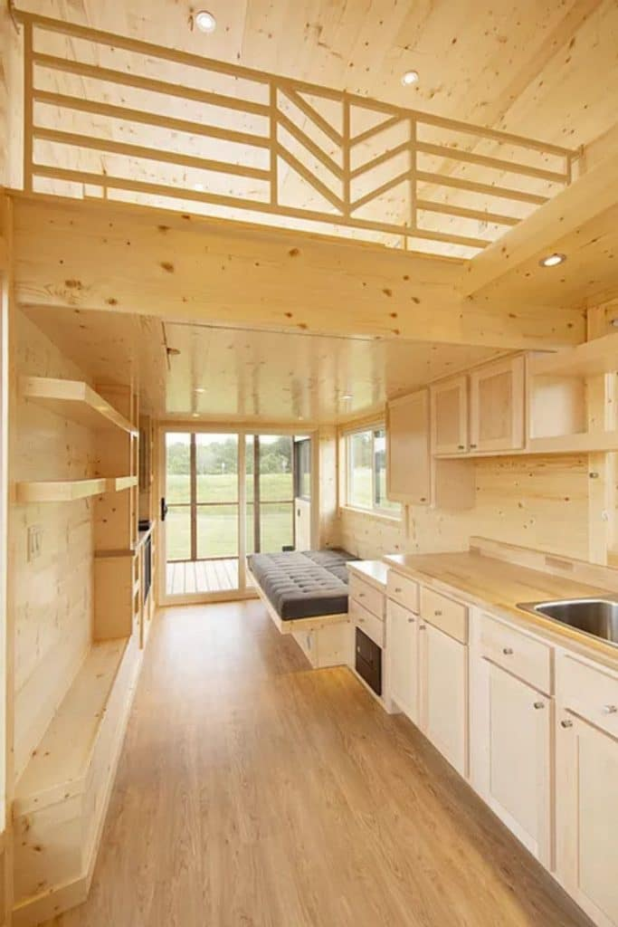 View down length of natural wood interiro of tiny home with kitchen on right